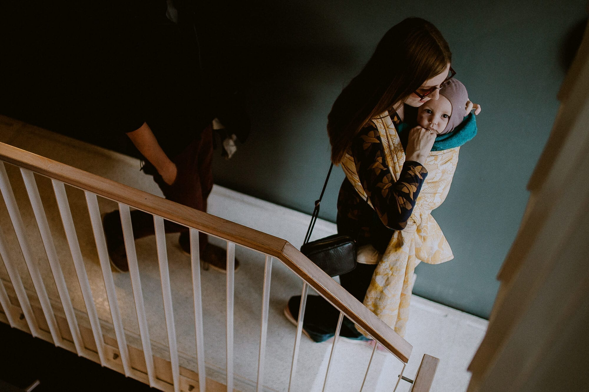Two persons are walking down a stairway. The woman is in front wearing her child in a woven baby carrier. The carrier is the all-cotten wrap Au by Levate wraps.