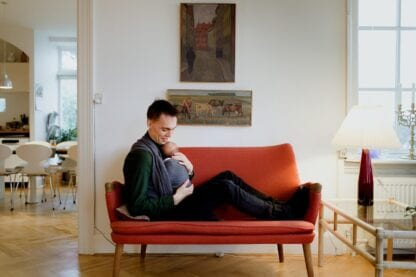 A man sitting on the couch wearing his baby in a front wrap cross carry, fwcc. The wrap is Disguise by Levate wraps.