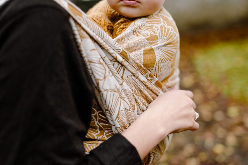 A baby wrapped in a yellow wrap by Levate.