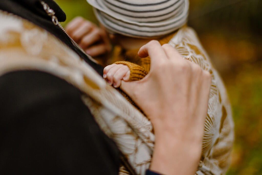 A baby hand in a baby sling.