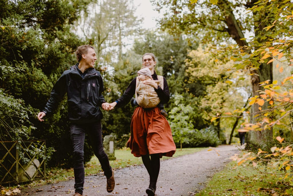 A couple running in a park while toddlerwearing.