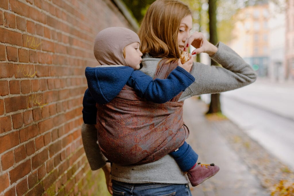 A mother feeding her toddler in a baby sling.