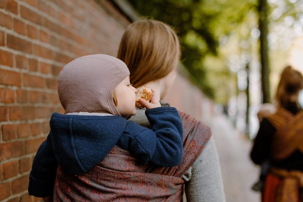 Toddler eating a bun in a woven wrap.