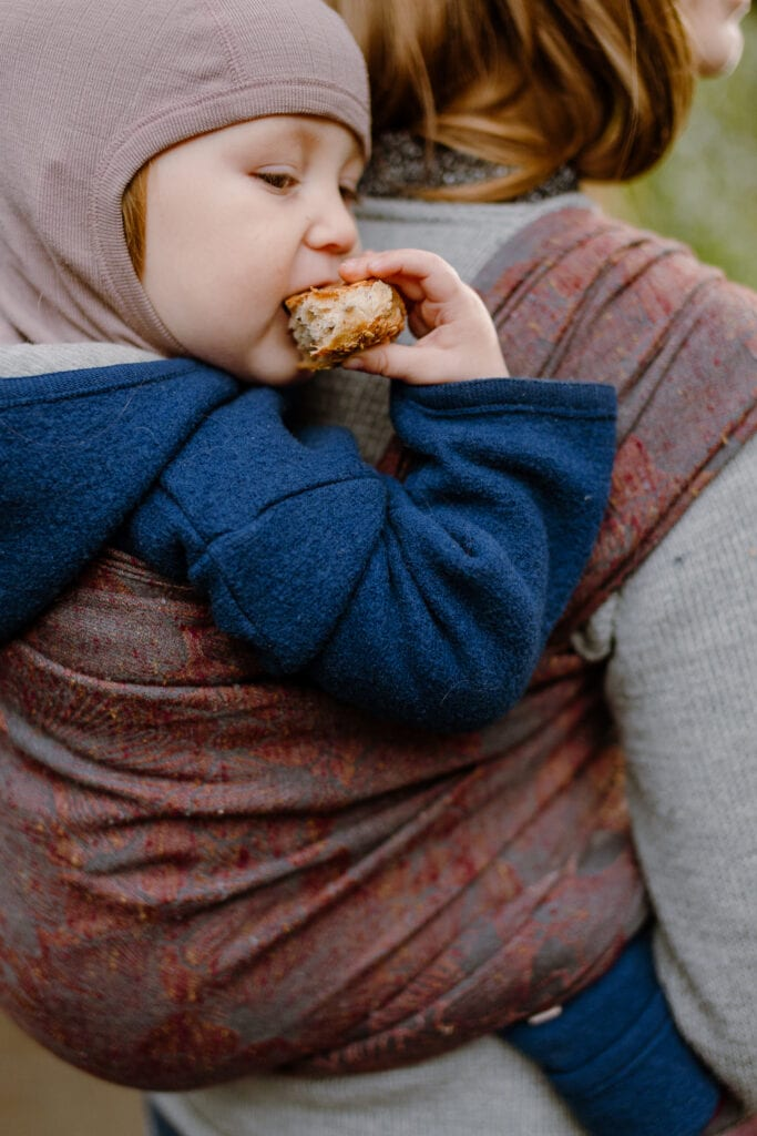 Toddler being carried in Levate wraps Frida while eating.