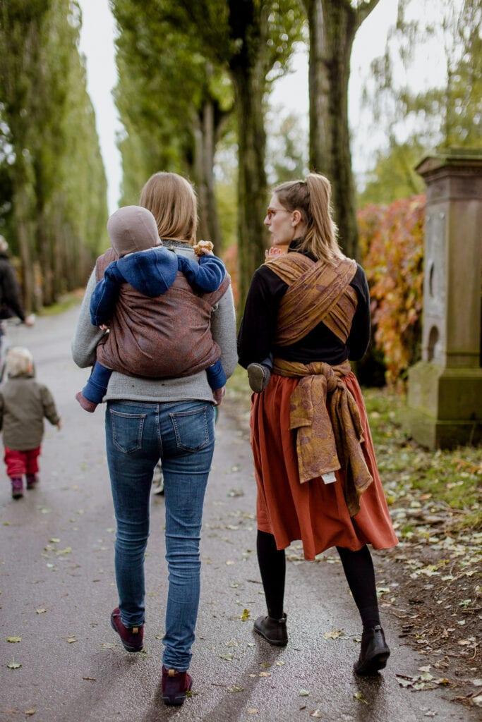 Two mother's babywearing in a park.