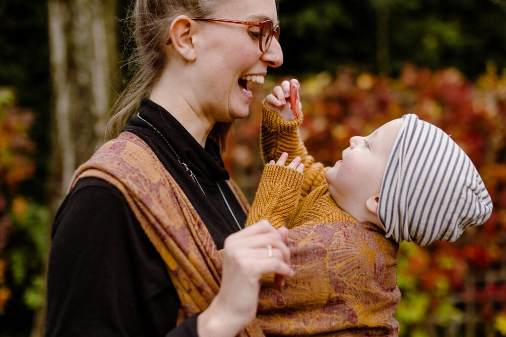 A toddler showing a red leaf to his mother from the wrap he is carried in.