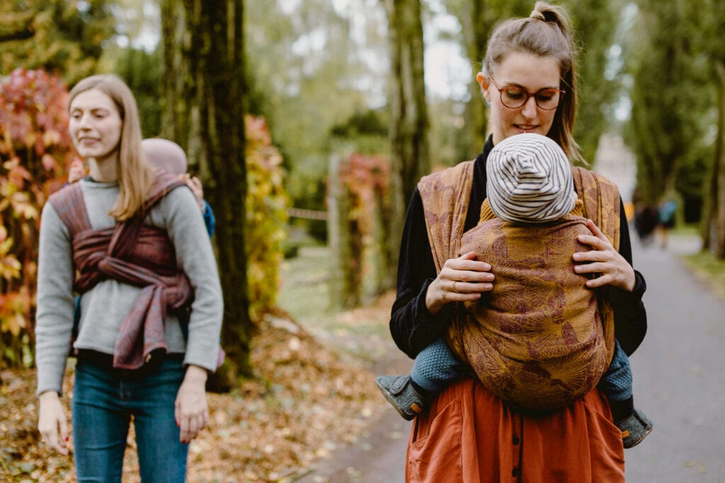 Two friends carrying their babies in woven wraps.