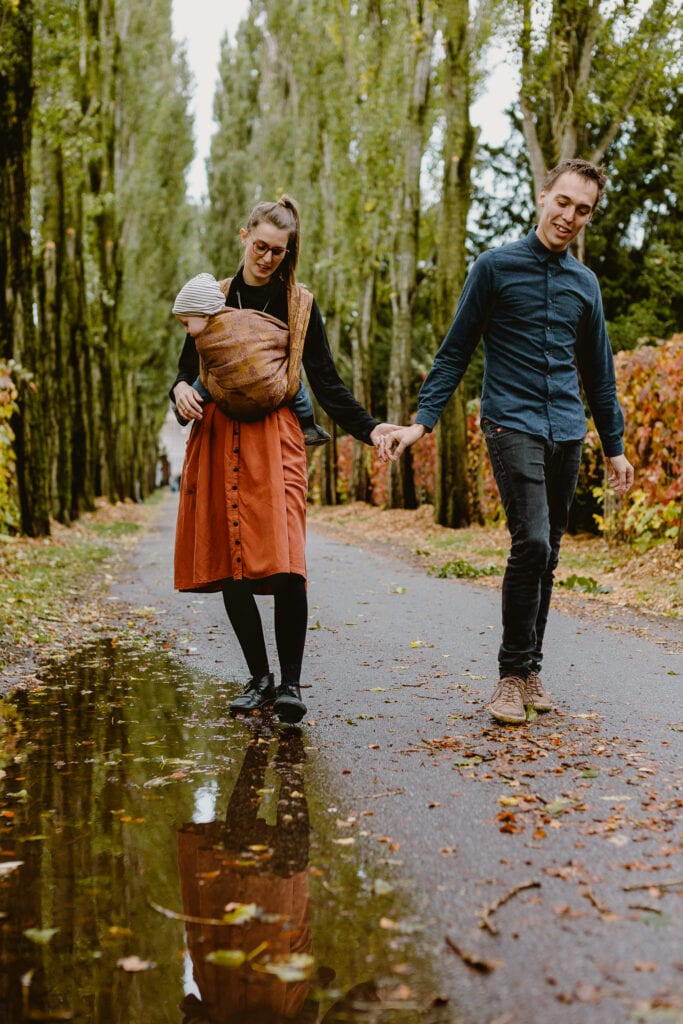 A couple walking on an allé. The mother is wearing a baby in a front wrap cross carry and the baby is studying the puddles on the ground.