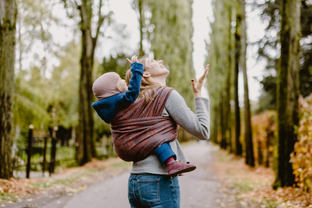 A mother and her boy checking if it rains. The boy is on her back in a baby sling.