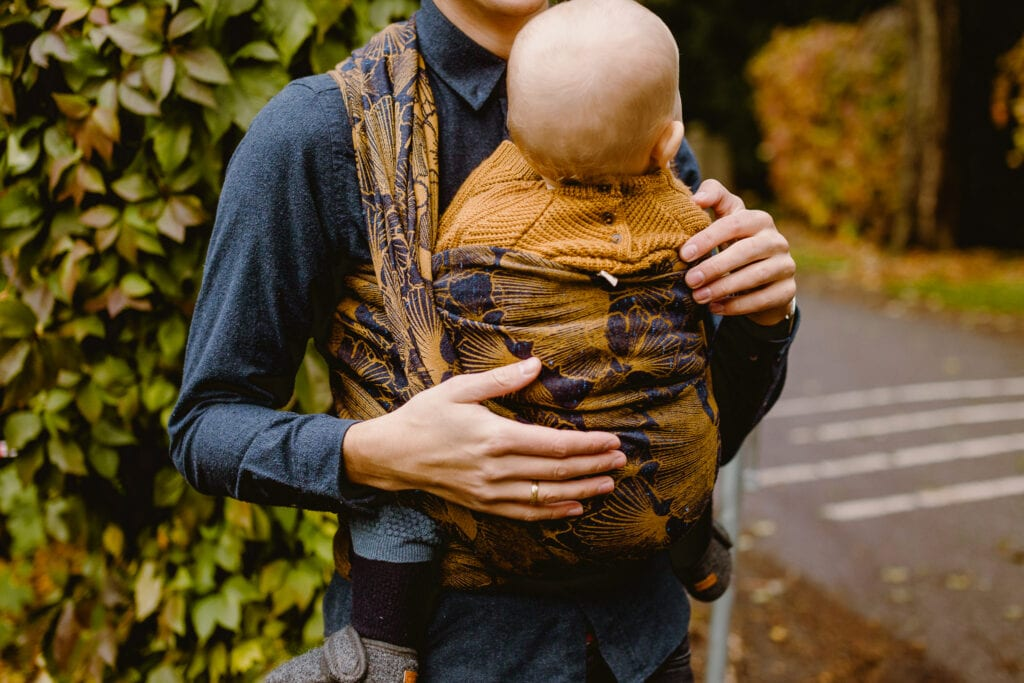 A man carrying a toddler in Leves of Ginkgo Mejse.