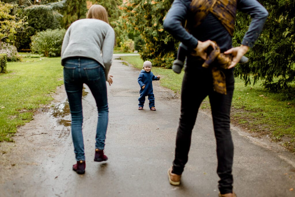 Two adults chasing a toddler.