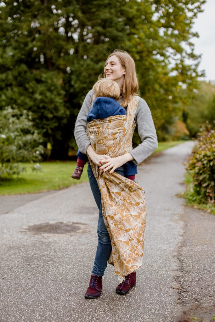 A mother tying a front wrap cross carry.