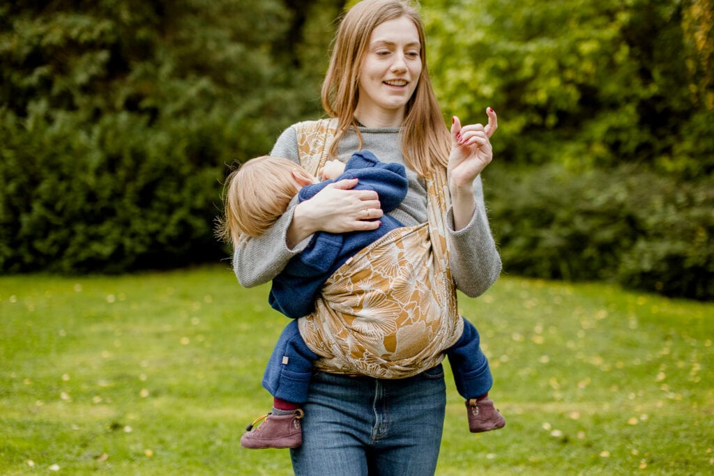 Breastfeeding toddler in a baby carrier
