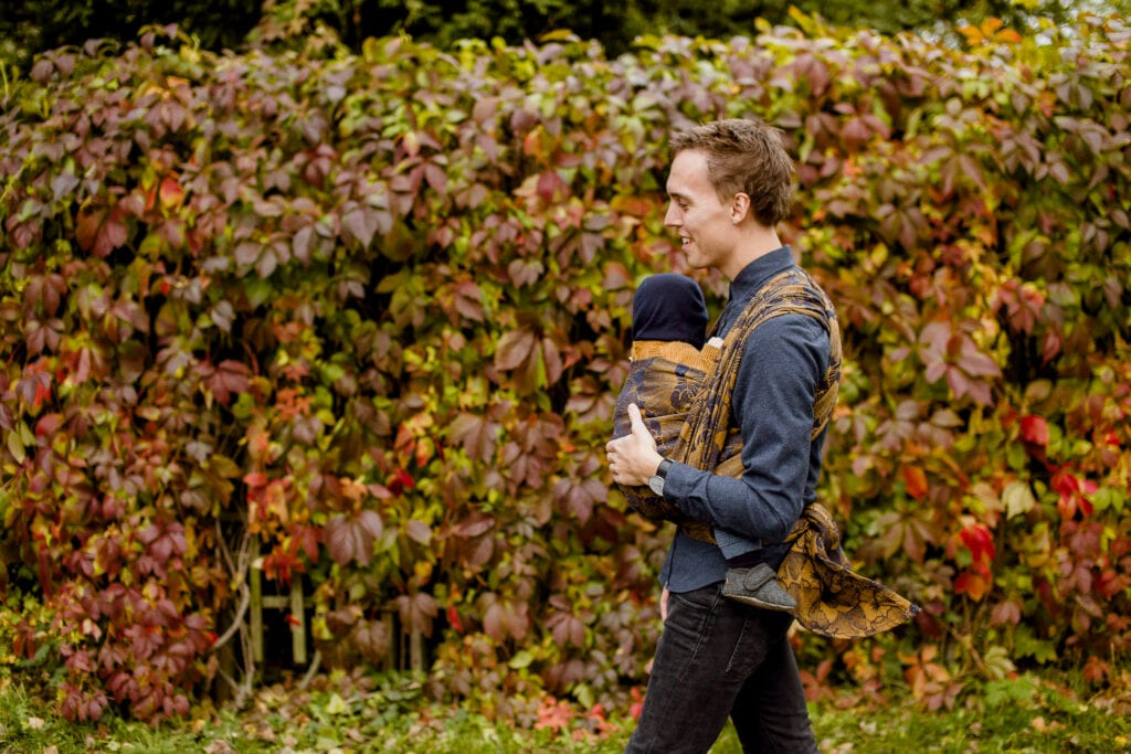 A man walking in a park with his baby on the front.