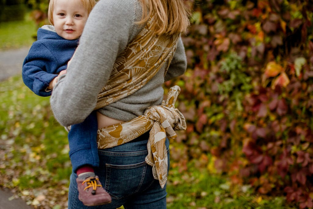 Toddler being carried in sling by Levate.