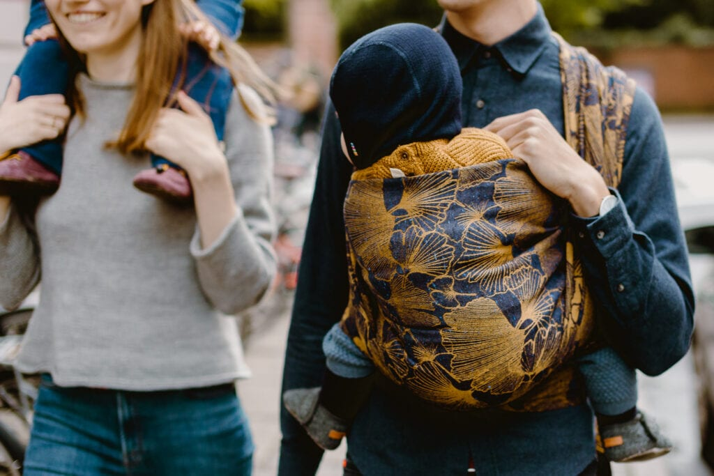 A man carrying his son i a baby sling.