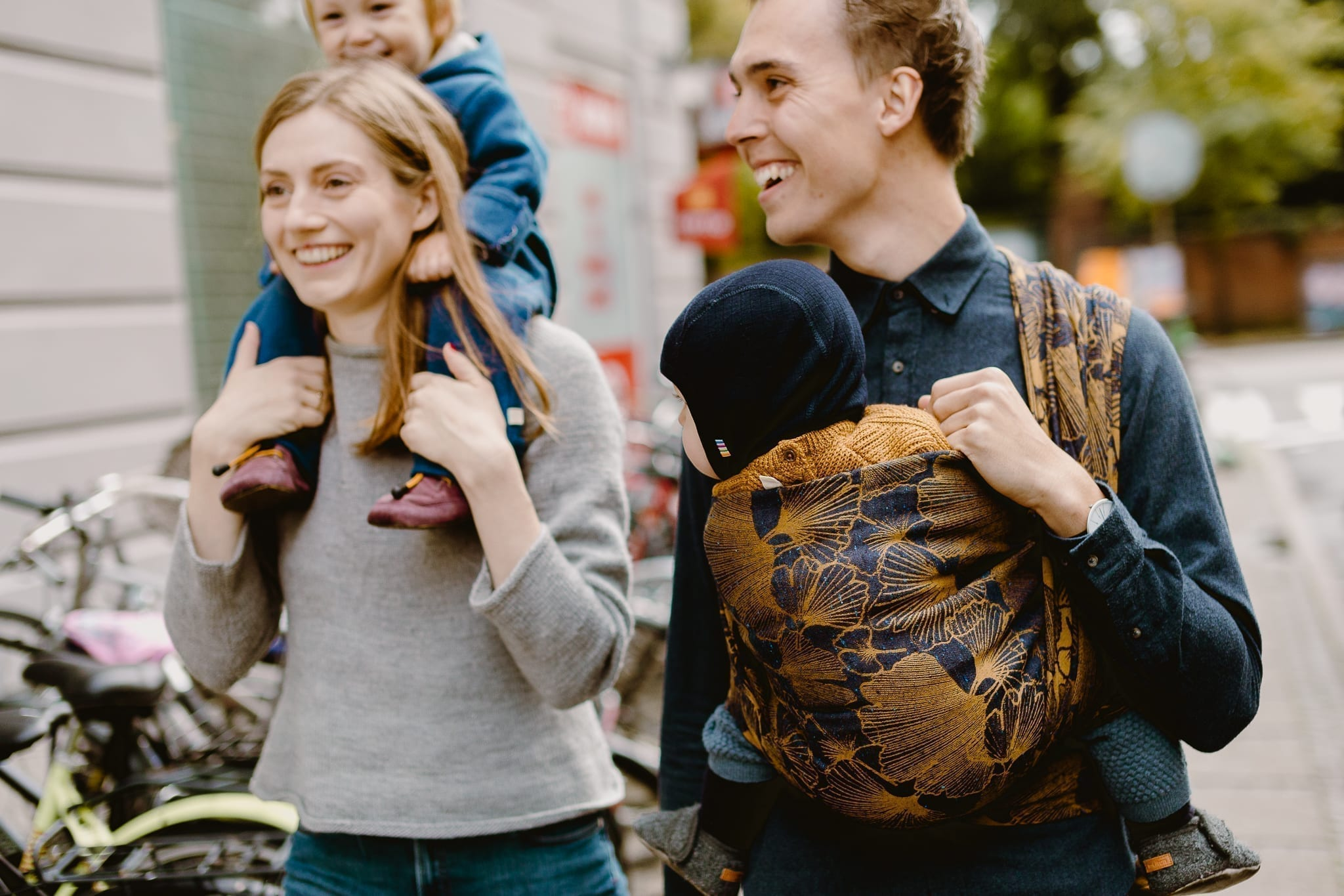A man and a woman walking down the street. The woman is carrying her son on her shoulders and the man is wearing his baby in a baby sling by Levate.