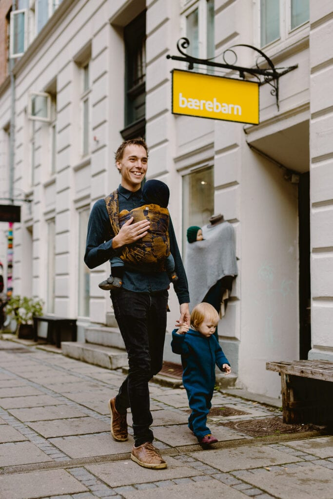 A father wearing his son in a woven wrap by Levate while holding a bigger toddler boy in his hand.