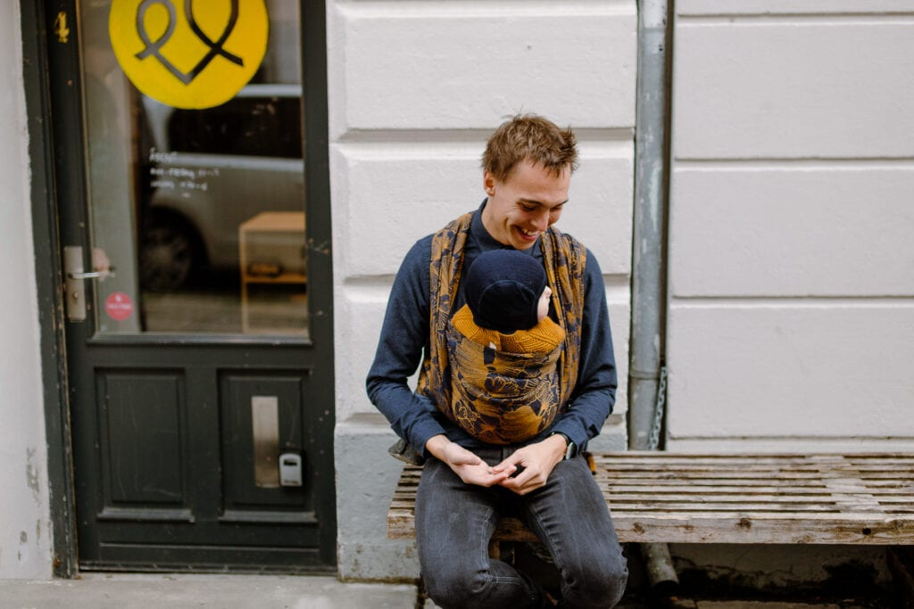 A man sitting on a bench with his son in Levate wraps Leaves of Ginkgo Mejse.