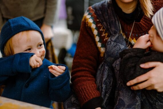 A toddler boy pointing and smiling at a mother wearing her boy in Morpho by Levate.