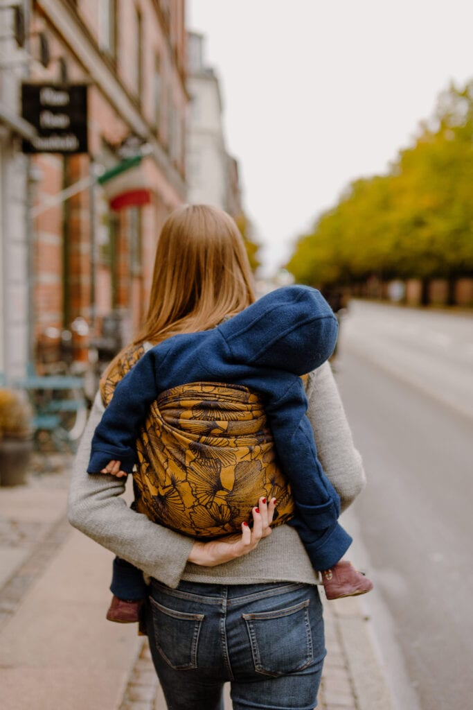 A mother carrying her sleeping son in a ruck carry at Jagtvej in Copenhagen
