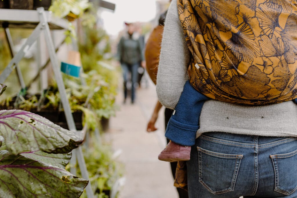 A mother is shopping with her baby on her back in a Ruck carry.