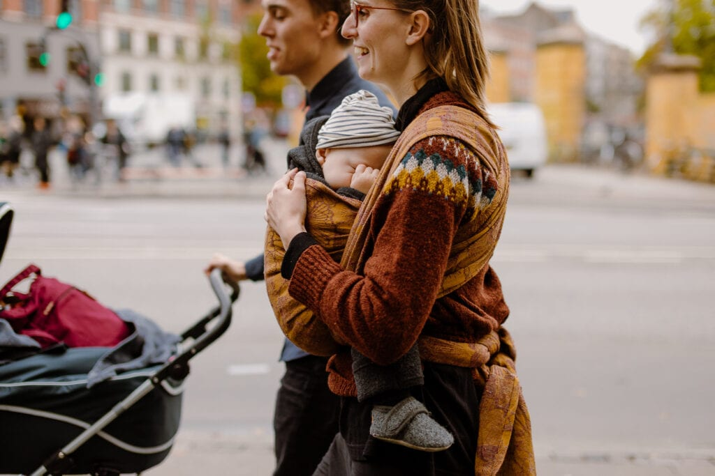 A couple walking on Nørrebro. The man is pushing a stroller and the mother is carrying her baby in Levate Leaves of Ginkgo Ferric.