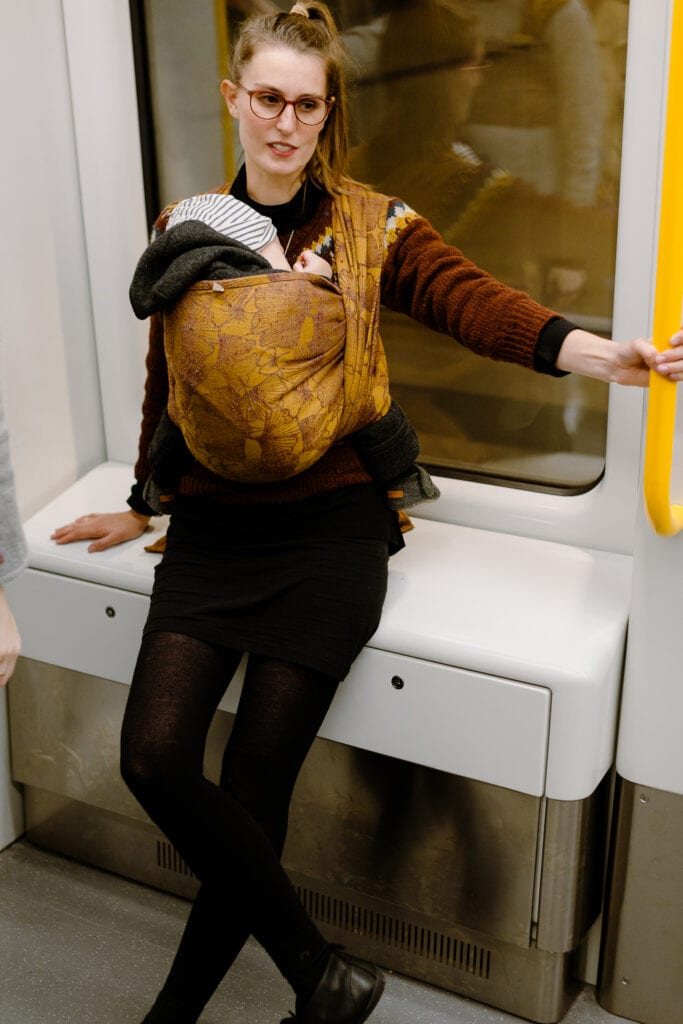 A mother wearing her sleeping baby in Ferric by Levate on the Copenhagen metro.