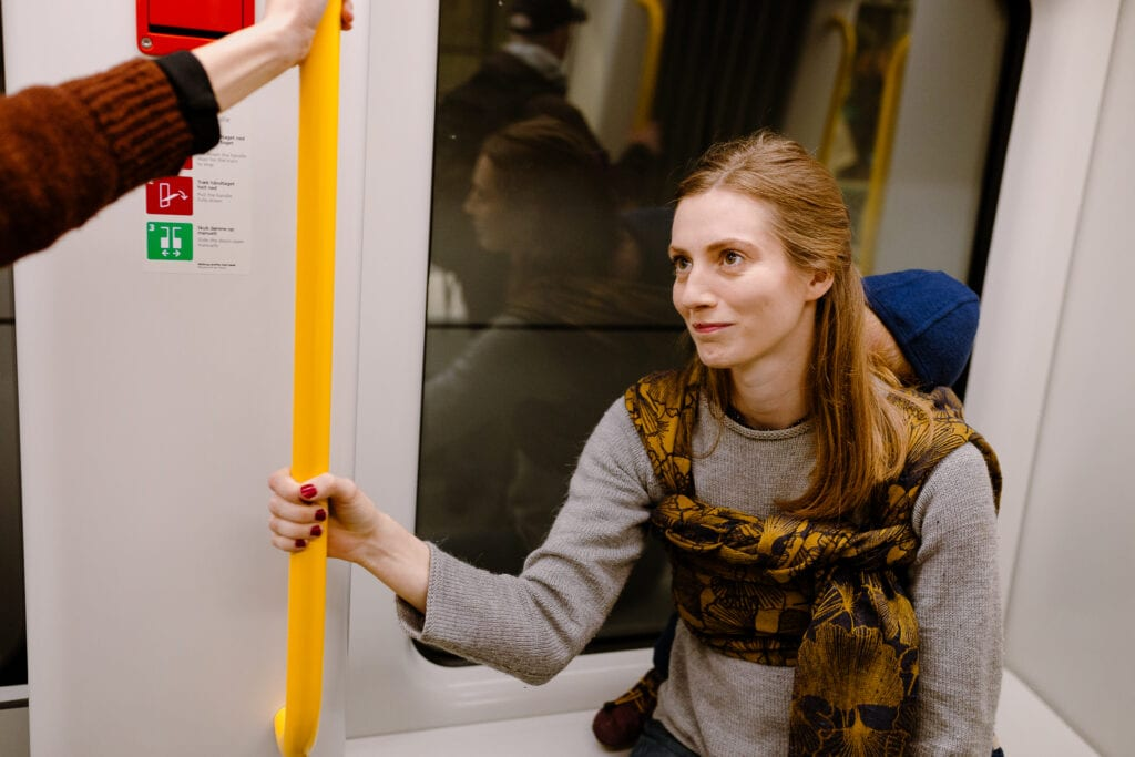 A mother on the Copenhagen Metro with her son sleeping on her back in Mejse by Levate.