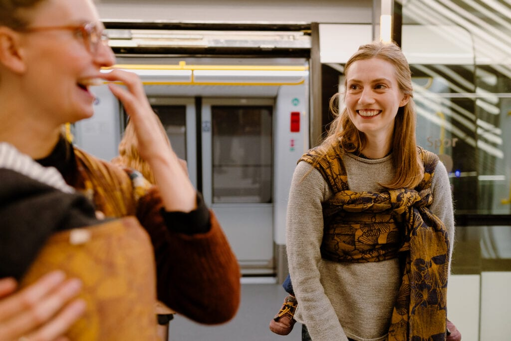 Two mothers smiling as thei are about to enter the Copenhagen metro with free hands and sleeping babies in wraps.