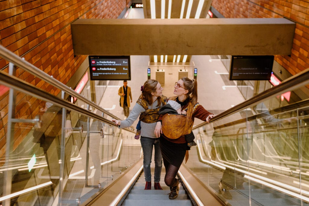 Two mamas exiting the Copenhagen metro by the escalator, both mothers have sleeping kids in a sling.