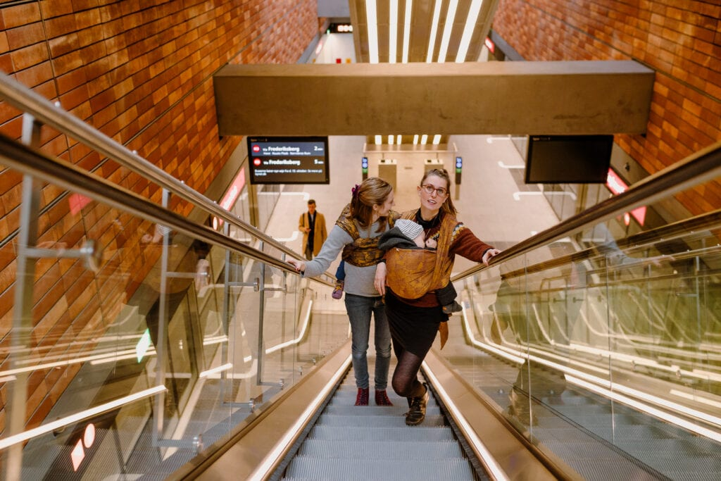 To mothers taking the escalator out of the Copenhagen metro with sleeping kids.