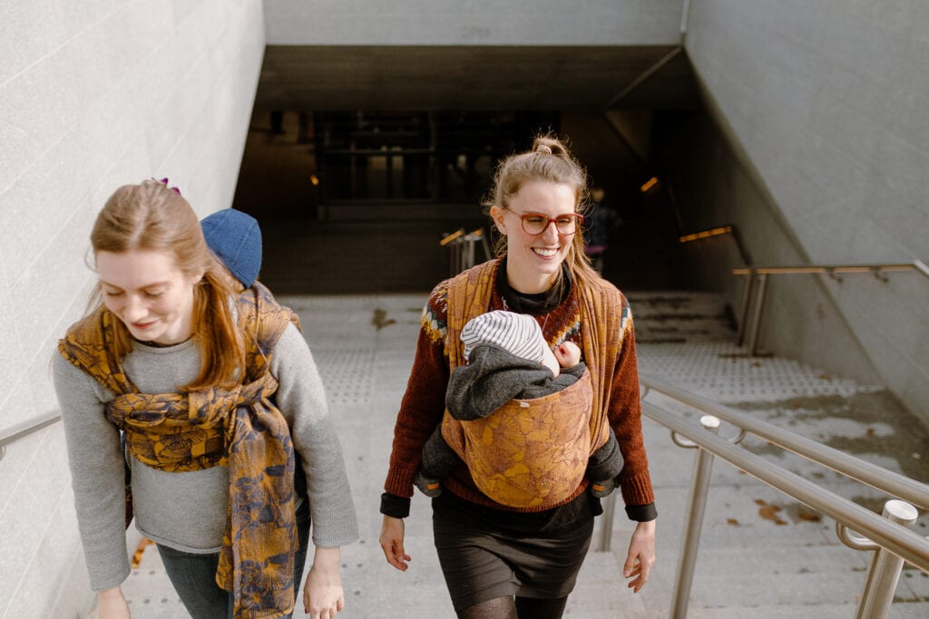 Two women exiting the Copenhagen metro with free hands and sleeping kids in their slings.