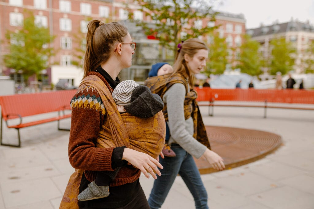 Two women carrying their sons are enjoying hands-free chat with their babies wrapped in woven slings by Levate.