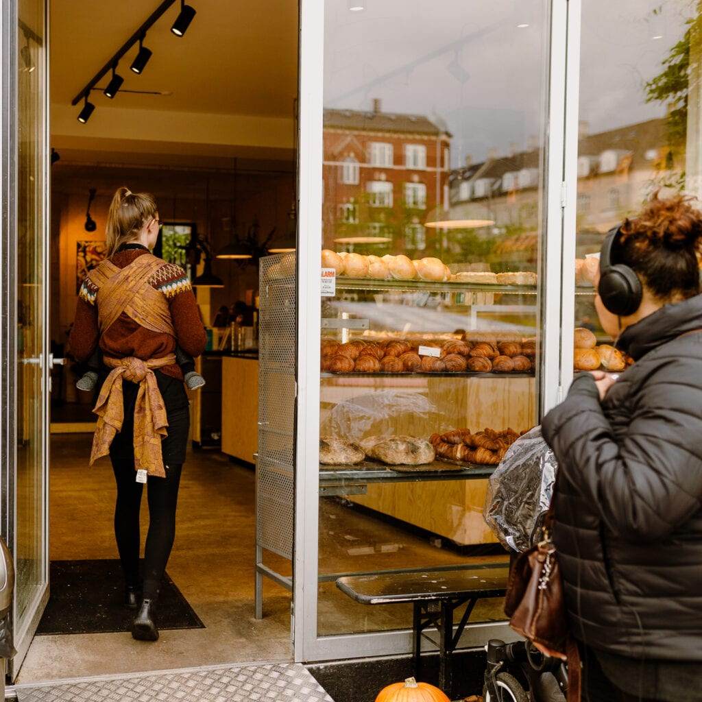 A woman entering a bakery in Copenhagen. Her toddler son is wrapped in Ferric by Levate.