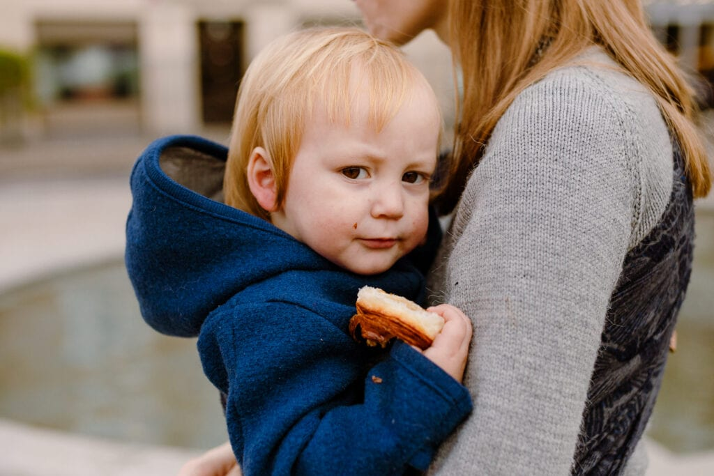 A toddler boy enjoying a bun while being carried by his mother in A baby sling by Levate.
