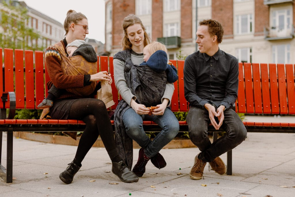 Two mothers and their sons sitting on a bench wrapped in two different wraps from Levate.