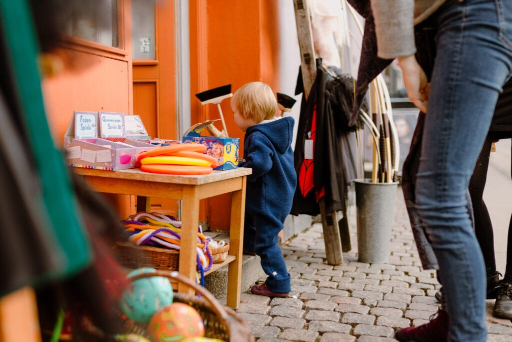 A boy entering toy shop with his mother in the streets of Copenhagen.