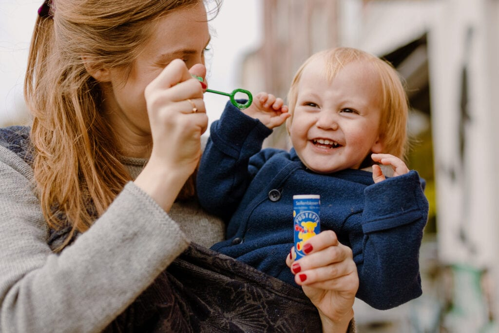 A woman cheering up her son by blowing soap bubbles while he is wrapped on her front. Her son is smiling.