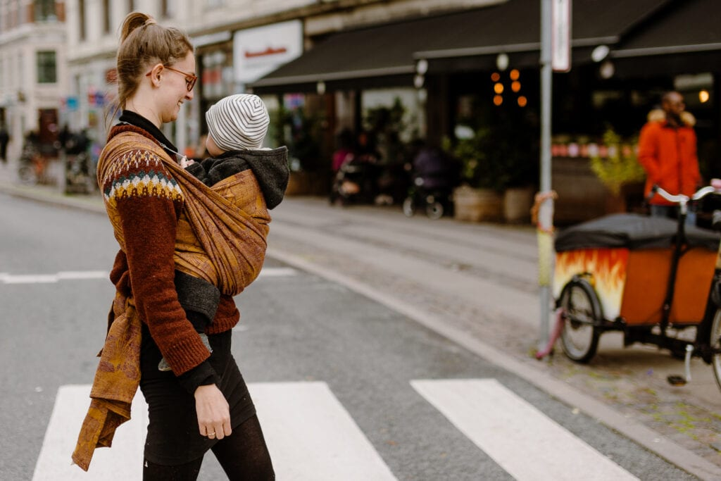 A woman crossing the street in Copenhagen with her baby wrapped in a front wrap cross carry.